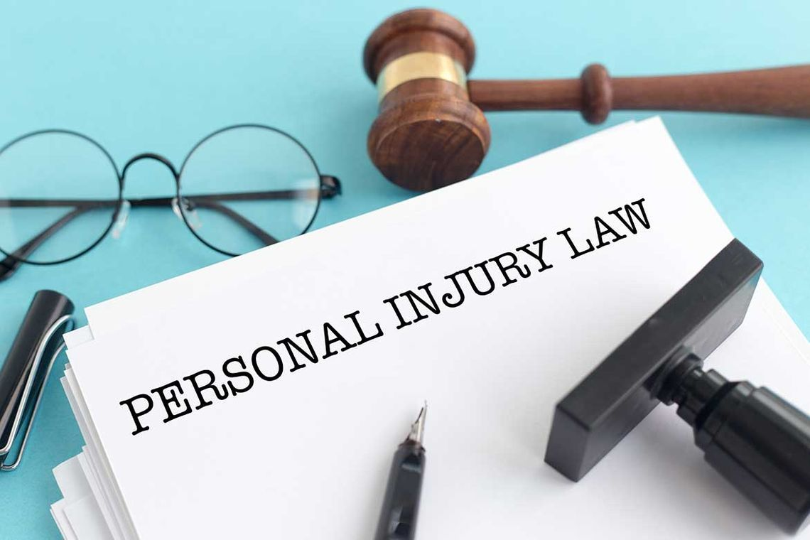 a stack of papers with the words personal injury law on the front with a gavel, and glasses nearby